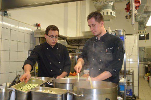 Chefkoch David Esser (rechts) hilft Mohamed Zamantouti bei der Zubereitung einer Suppe. - Foto: LWL/Hötte