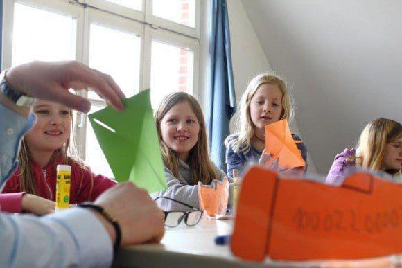 Ferienspiele: Aus einem quadratischen Blatt Papier ein Windrad zu falten ist zwar gar nicht so leicht, macht den Kindern aber viel Spaß. Foto: Stadt Rietberg