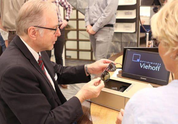 Augenoptikermeister Jürgen Elixmann von Optik Viehoff legt die Sonnenbrille in das Gerät ein, um den Testvorgang zu starten. Foto: FH Münster/Pressestelle