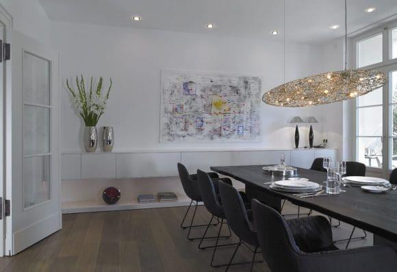 Durch die meist offenstehenden Berliner Doppeltüren, die an eine Villa aus den 1930er-Jahren erinnern, gelangt man ins Esszimmer. Urig und markant präsentiert sich dort der massive Tisch aus schwarz geköhlter und anschließend geölter Eiche von Janua. Optischer Kontrapunkt ist das weiß lackierte, frei hängende Lowboard an der Wand. Die 5,50 Meter breite Anfertigung stammt – wie alle Regale, Schränke, Schiebtüren und die Kücheneinrichtung – aus der haus- eigenen Tischlerei.