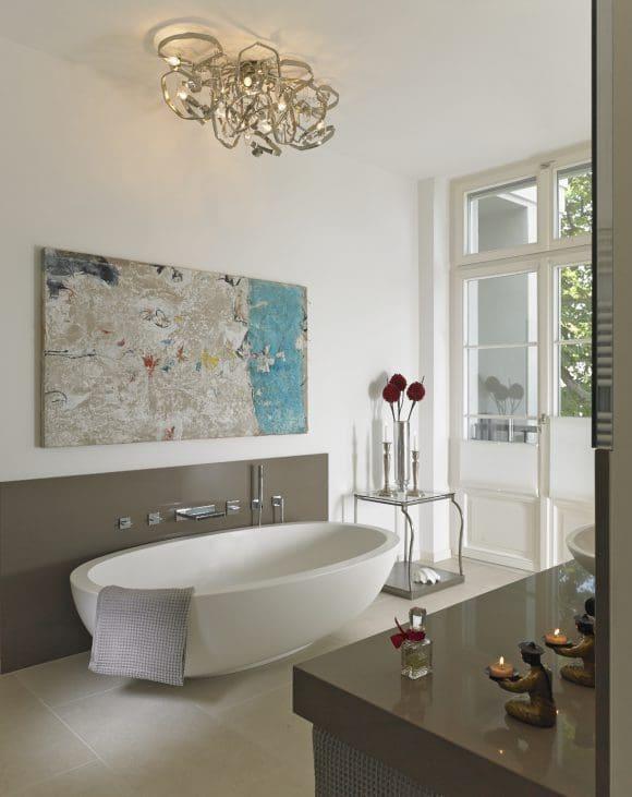 """Im Badezimmer ist die luxuriöse freistehende Badewanne """"Epona"""" von Domovari der Star. Ins rechte Licht gesetzt wird sie von der opulenten Deckenleuchte """"Delphinium"""" aus der Designschmiede von Brand van Egmond."""