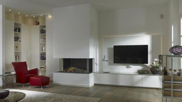 Vor einer maßgefertigten Bücherwand aus Lack befindet sich eine gemütliche Leseecke, nebenan die TV- und HiFi-Kombination mit integrierten Aufbewahrungslösungen. Zur Atmosphäre trägt zudem der modern gestaltete Kamin aus dem Kaminhaus Grewing bei.